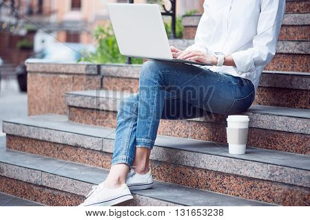 Modern life.  Confident young woman using a laptop and drinking coffee while sitting on stairs