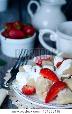 Cottage cheese dumplings with strawberries on background top view with sour cream