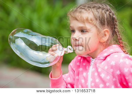 Five-year Girl Inflates A Large Soap Bubble