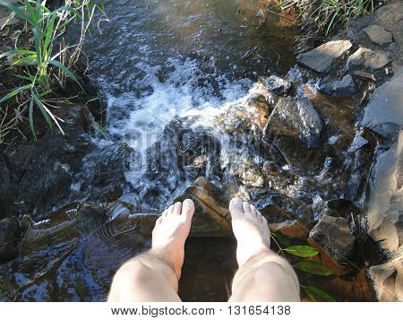 Legs of a man resting above a stream.