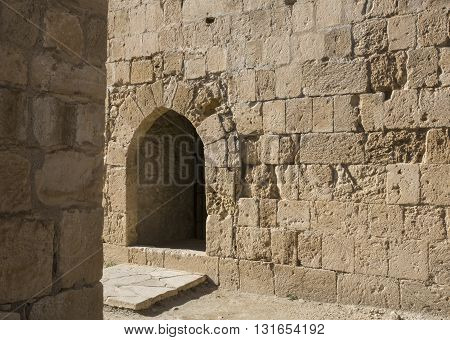 Arch window in old stone wall of medieval castle horizontal image with copy space