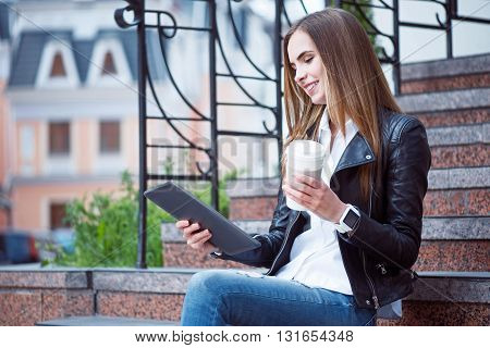 Being modern.  Smiling and content young woman using a digital tablet and drinking coffee while sitting on the stairs