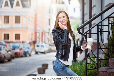 Being close to my friends and relatives.  Positive and cheerful woman speaking per cell phone and holding a cup of coffee while being in a big city and standing near stairs