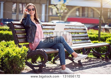 Relaxing moments.  Smiling and positive young woman using a laptop while sitting on a bench and being in a park