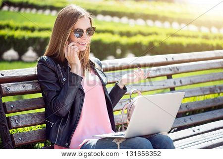My lifestyle. Smiling and content young woman speaking per sell phone and using a laptop while sitting on a bench and being in a park