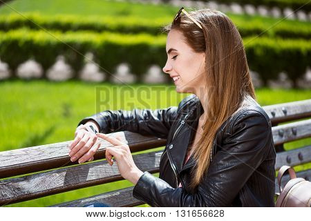 What time is it. Cheerful and positive young woman looking at her smart watch while sitting on a bench and waiting on somebody