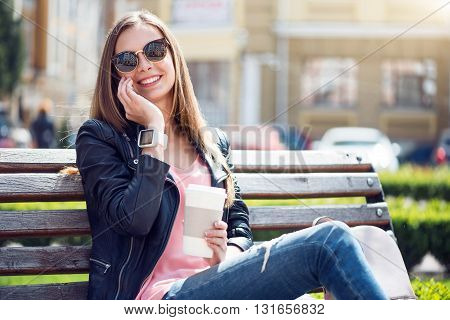 Modern times. Glad and smiling young woman making a phone call while sitting on a bench in a park and drinking coffee
