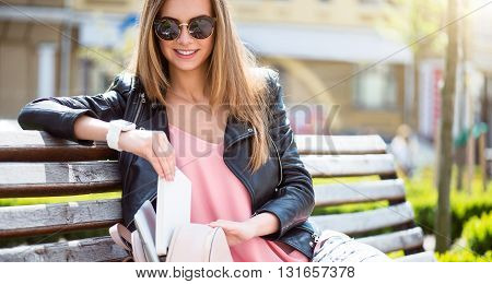 Time to go. Positive and merry young woman packing her books in a bag while sitting on a bench in a park