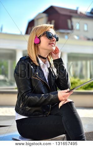 carefree hipster girl listening to music with tablet