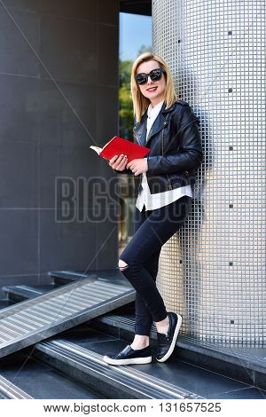 young hipster girl standing with red book