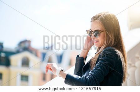 It is time to make a move. Smiling and glad young woman looking at her smart watch and thinking about her list to do for today with some buildings in a background