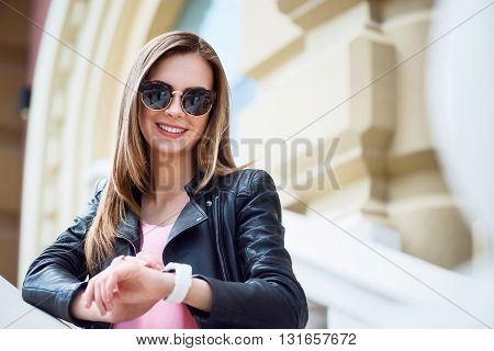 My favorite watch. Positive and merry young woman looking at her smart watch and thinking about plans for today