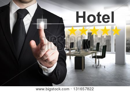 businessman in modern office pushing touchscreen hotel rating stars
