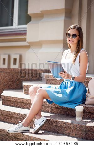 During my day. Cheerful and positive modern young woman using a  digital tablet while drinking coffee and sitting on the stairs