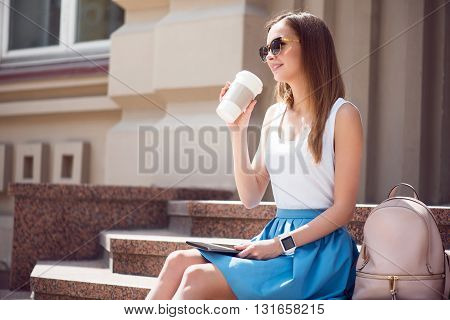 Having nice day. Smiling and positive modern young woman drinking nice coffee and using a digital tablet while and sitting on the stairs