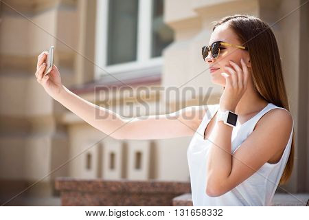 Posing for selfie.  Cheerful and happy modern young woman using her cell phone while making a selfie