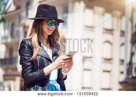Fashion lady.  Cheerful and positive modern young woman using her cell phone and sending messages her best friend being in a big city