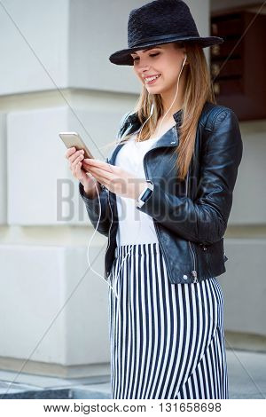 Relaxing sound recordings.  Positive and smiling modern young woman using her cell phone while listening to music and being in a very good mood