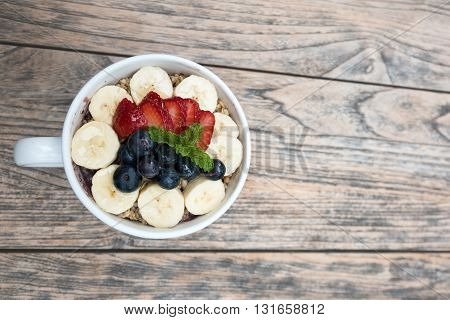 Very delicious acai bowls with fresh fruit strawberry, blueberry, banana and peppermint leaves on top in cute white cup on the wooden table. this smoothie dessert is good for summer in Hawaii.