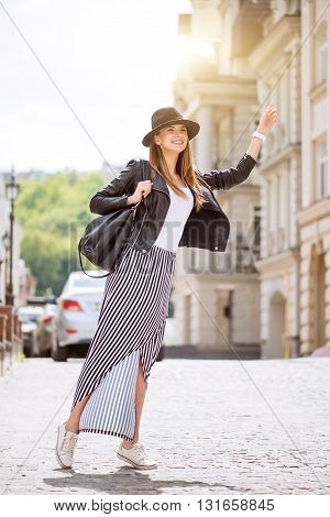 Hitchhiking.  Cheerful and very happy modern young woman hailing a taxi being in a big city
