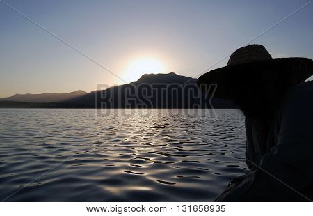 Sunrise on the boat with woman silhouette wearing sunhat