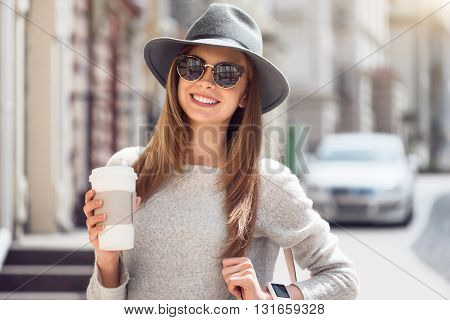 Coffee time. Smiling and positive modern young woman drinking nice coffee while being outside and walking around the city