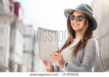 Technologies in our life.  Smiling and cheerful modern young woman using her digital tablet while being outside