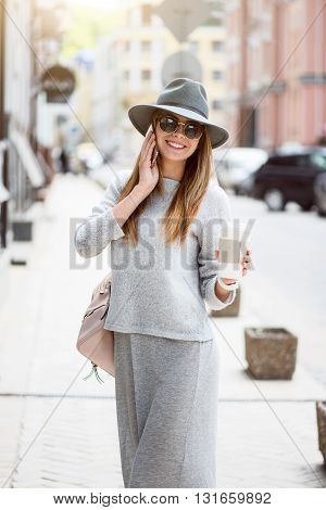 Phone impact.  Positive and cheerful modern young woman speaking per cell phone while drinking nice coffee and being outside