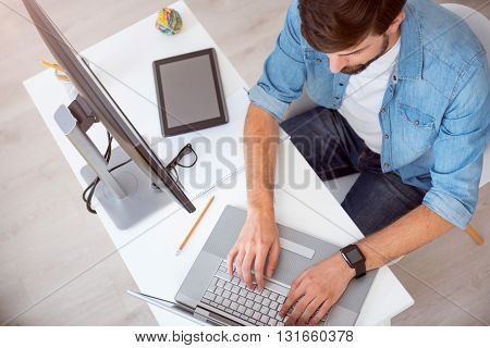 It is a work time. Handsome young man concentrating on his work while sitting at the table and tapping on his laptop