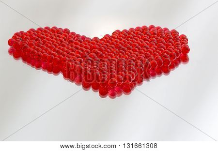 A red heart made of plastic marbles with a reflection