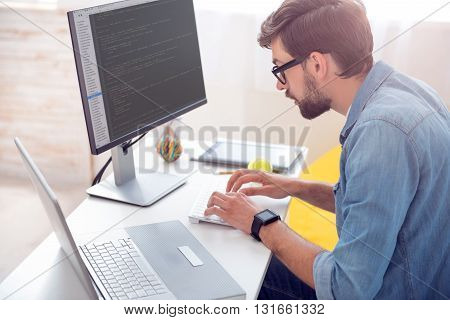 Time to work hard. Concentrated young man involved in programming while sitting at the table