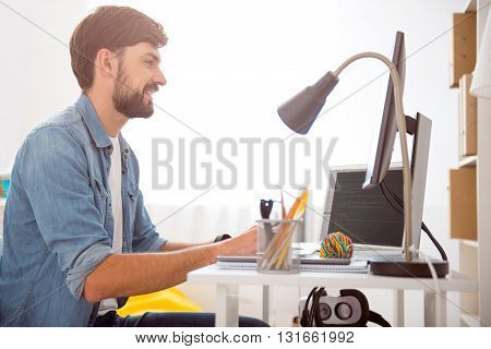 Working time like a pleasure. Cheerful young guy looking at the screen with codes while sitting at the table