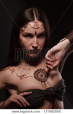 Mehendi. Studio portrait of brunette with exotic appearance