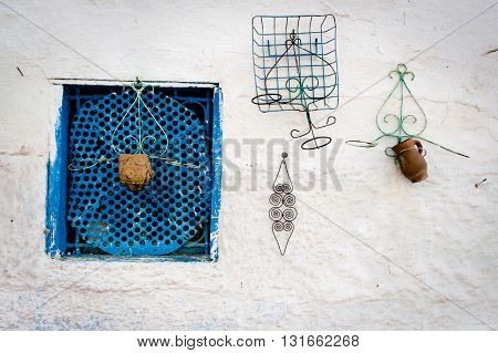 Blue typical window on white wall in Fez, Morocco, Africa