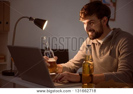 After work. Restful bearded guy smiling and looking at the laptop while having a beverage in the evening