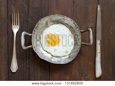 Fried egg in a old frying pan with fork and knife on wood