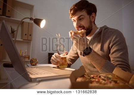 So interesting. Cheerful young guy eating a slice of pizza and drinking a beverage while watching a film on the laptop in the evening