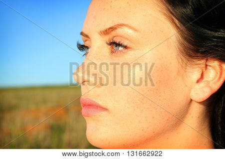 Portrait of a beautiful brunette girl on nature