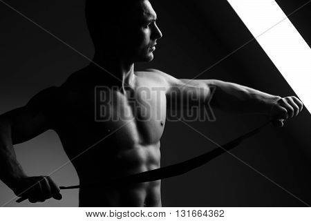 Sexy young man with muscular body and bare torso posing near window holding leather belt black and white