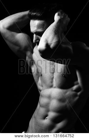 Male bare torso and sexy muscular body of young handsome man posing in studio black and white