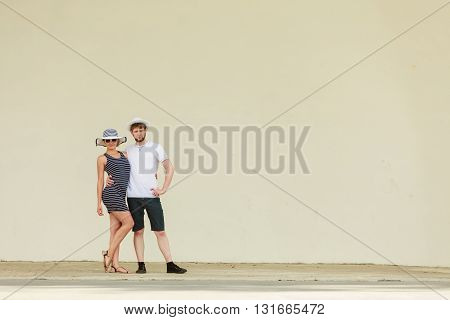 Fashion couple posing outdoor on stage. Woman in striped dress and hat and man in white shirt.