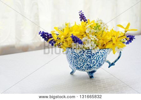 Teacup full of a spring flower bouquet.