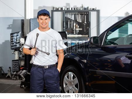 Happy Mechanic Holding Rim Wrench At Garage
