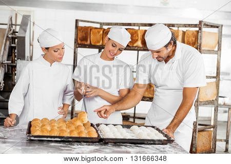 Baker's Analyzing Breads At Table In Bakery