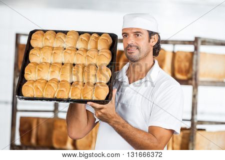 Baker Showing Breads In Baking Tray While Looking Away