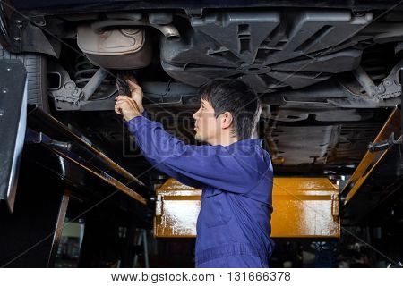 Mechanic Examining Underneath Lifted Car