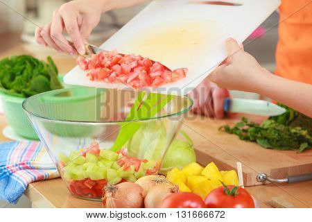 Healthy eating vegetarian food cooking dieting and people concept. Couple in kitchen at home preparing fresh salad slicing vegetables on cutting board throwing into bowl