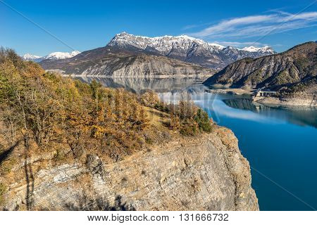 Serre-Poncon Lake and Grand Morgon in winter with view of the village of Sauze Le Lac on a cliff plateau. Hautes-Alpes, French Alps, France
