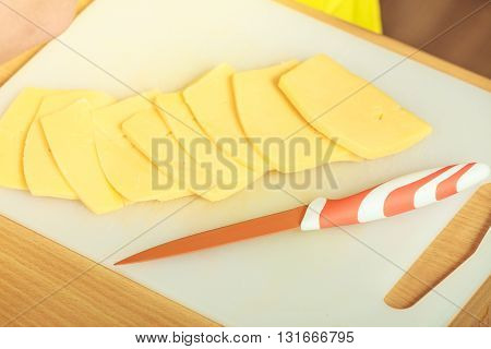 Cooking food and home concept. Piece of cheese on kitchen board close up