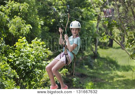 Happy little girl riding a zip line in a lush tropical forest on a fun summer vacation